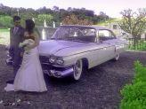 Casal de noivos em pose na dianteira de carro antigo de Filipe Alves - Filipe Alves Classics