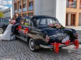 Em pose, noivo sentado no capot de carro, junto de noiva, em fotografia de Foto Aguiarense - Foto Aguiarense