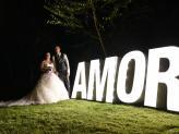 Noivos à noite junto a placa AMOR iluminada em fotografia de Foto Aguiarense - Foto Aguiarense